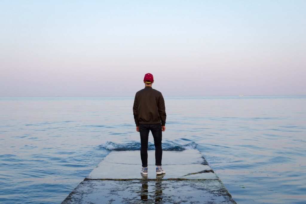 """man standing on concrete dock facing sea"" by Nicholas Barbaros on Unsplash"